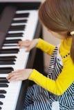 La niña en alineada amarilla juega el piano Imagen de archivo libre de regalías