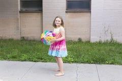 La niña en arco iris coloreó el vestido y los pies desnudos que sostenían la pelota de playa clara del vinilo Fotografía de archivo libre de regalías