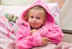 La niña en cama mira en la cámara Fotografía de archivo