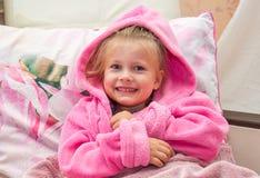 La niña en cama mira en la cámara Imagen de archivo