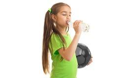La niña en camisa verde bebe el agua de una botella Imagenes de archivo