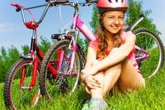 La niña en casco rojo se sienta en un prado Imagenes de archivo