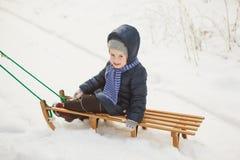La niña en chaqueta del invierno se sienta en el trineo en bosque nevoso Foto de archivo libre de regalías