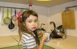 La niña en cocina lava los platos Foto de archivo libre de regalías
