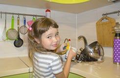 La niña en cocina lava los platos Imagen de archivo