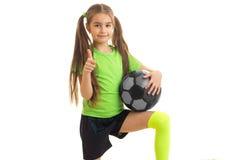 La niña en deportes uniforma con el balón de fútbol en pulgares de las demostraciones de las manos para arriba Foto de archivo libre de regalías