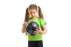La niña en deportes verdes uniforma con el balón de fútbol en manos Foto de archivo