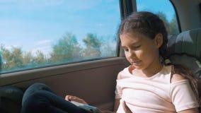 La niña en el coche con un medio social de Internet de la tableta va en un viaje muchacha en el movimiento del transporte del via metrajes