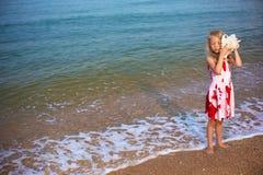 La niña en el mar escucha la concha de berberecho Imágenes de archivo libres de regalías