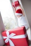 La niña en el sombrero de Papá Noel aumentó el regalo sobre su cabeza que se sentaba por la ventana Imagen de archivo libre de regalías
