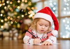 La niña en el sombrero de Papá Noel escribe la letra a Santa Claus Fotos de archivo libres de regalías