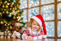 La niña en el sombrero de Papá Noel escribe la letra a Santa Claus Foto de archivo libre de regalías