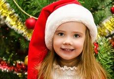 La niña en el sombrero de santa con el presente tiene una Navidad Imagen de archivo