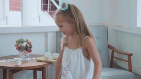 La niña en el vestido blanco está haciendo girar en casa en la cámara lenta almacen de metraje de vídeo