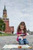La niña en el vestido elegante que se sienta cerca del Kremlin Fotos de archivo