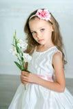 La niña en el vestido y la flor blancos está presentando en un s hermoso Fotos de archivo libres de regalías