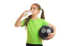 La niña en fútbol que juega uniforme del verde con la bola y las bebidas riegan Imágenes de archivo libres de regalías