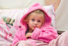 La niña en la cama desconcertante mira en la cámara Fotos de archivo