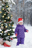 La niña en la madera cerca del árbol de navidad adornado imagen de archivo