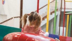 La niña en la tubería rueda con las diapositivas en el área de juego almacen de video