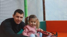 La niña en la tubería rueda con las diapositivas en el área de juego Papá e hija que sonríen y que miran la cámara metrajes