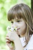 La niña en los wildflowers que huelen del parque Imagenes de archivo