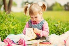 La niña en parque de la primavera lee el libro adentro imagen de archivo