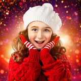 La niña en ropa del invierno, piensa en Papá Noel Enciende el fondo Fotos de archivo libres de regalías