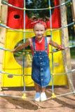 La niña en traje azul del dril de algodón y camiseta roja está jugando en el patio foto de archivo