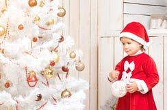 La niña en traje rojo adorna el árbol del Año Nuevo con la bola Fotografía de archivo