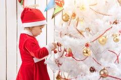 La niña en traje rojo adorna el árbol del Año Nuevo con la bola Imagenes de archivo