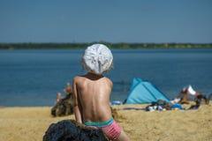 La niña en troncos que nadan rosados y un sombrero blanco mira a la gente en la playa fotografía de archivo libre de regalías