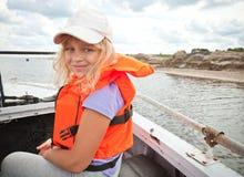 La niña en un bote pequeño desgasta el chaleco salvavidas rojo Fotografía de archivo libre de regalías