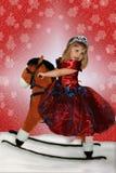 La niña en un caballo del juguete fotografía de archivo