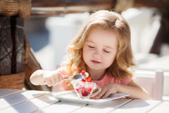 La niña en un café del verano Foto de archivo