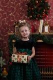 La niña en un día de Años Nuevos está alrededor de la chimenea ella está sosteniendo un regalo Sitio adornado con las decoracione Imagenes de archivo