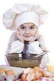 La niña en un delantal blanco se rompe cerca de la placa con los huevos Imagen de archivo libre de regalías