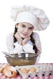 La niña en un delantal blanco se rompe cerca de la placa con los huevos Foto de archivo libre de regalías