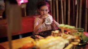 La niña en un restaurante cacerola-asiático limpia sus manos con una toalla mojada antes de comer almacen de metraje de vídeo