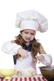 La niña en un sombrero blanco del delantal y de los cocineros amasa la pasta Foto de archivo