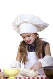 La niña en un sombrero blanco del delantal y de los cocineros amasa la pasta Imágenes de archivo libres de regalías