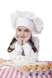 La niña en un sombrero blanco del delantal y de los cocineros amasa la pasta en th Fotos de archivo