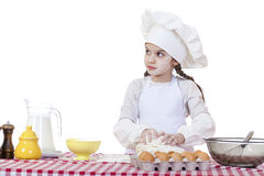 La niña en un sombrero blanco del delantal y de los cocineros amasa la pasta en th Fotografía de archivo libre de regalías