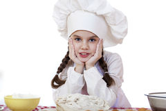 La niña en un sombrero blanco del delantal y de los cocineros amasa la pasta en th Foto de archivo