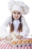 La niña en un sombrero blanco del delantal y de los cocineros amasa la pasta en th Fotos de archivo libres de regalías