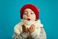La niña en un sombrero de la Navidad lleva a cabo sus manos juntas y sopla a9e3183acd4