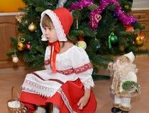 La niña en un traje del Caperucita Rojo y de una estatuilla Santa Claus sobre un árbol del Año Nuevo Imagenes de archivo