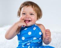 La niña en un vestido azul es que se sienta y de risa sosteniéndose el finger en su boca Imagen de archivo