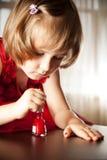 La niña en un vestido rojo pintó clavos con el esmalte de uñas Imagen de archivo