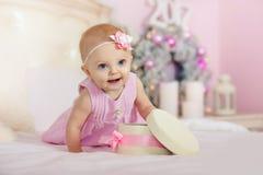 La niña en un vestido rosado con la flor en su pelo sonríe y abre los regalos de la caja en cama el fondo de Fotos de archivo libres de regalías